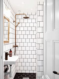 Bathroom with oversize hexagonal black-and-white subway tiles and gold touches