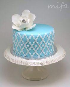 Pastel azul y flor blanca