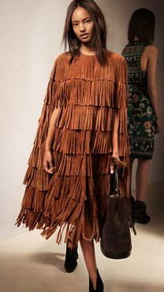 Burberry Prorsum Womenswear Autumn/Winter 2015 show | Burberry | LAYERED FRINGE CAPE A long cape in suede. Individual tiers of suede fringing add texture and contrast to the simple silhouette. The clean lines are complemented with a round neckline and concealed press-stud closure.