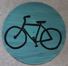 Show your love for biking by displaying this Painted Vinyl Record featuring a bicycle on a light teal background. Painted on a 12 LP.