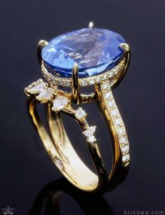 Raindrop Dazzle Engagement Ring. This engagement ring is both luxurious and organic in style and design. Diamonds of various sizes and shapes cling to the angled accent band. The large center stone sits in a diamond encrusted basket setting with pave set diamonds that continue down the sides of the shank.
