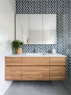Heres how to use a feature tile in a bathroom – create a stunning feature wall behind the vanity, add a wall hung custom made timber vanity and be smart with storage by adding face-level cabinetry