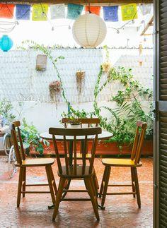 Apartamento em São Paulo com cara e clima de casa de praia tem como? Claro que sim. Nessa área externa, por exemplo, a decor ficou por conta das luzes e bandeirinhas penduradas, e muita planta.