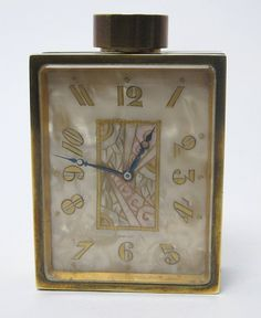 An Art Deco perfume bottle clock. Didisheim Goldschmidt Fils & Company for Juvenia, Swiss 'Le Numero 7 De Juvenia' made circa 1930, marble, mother of pearl and brass.