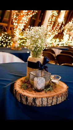 (Navy blue) mason jars filled with baby's breath, votives, and moss, on wood slices for a diy cute centerpiece.