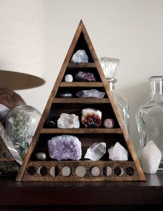 Moon phases triangle shelf. I like that shelf and the crystals on it.