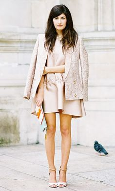 Blush-colored silk dress worn under a structured blazer draped over the shoulders