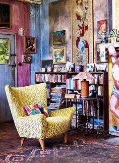 style hippie chic dans le salon avec peinture murale multicolore, fauteuil de couleur or et coussin à motifs bariolés