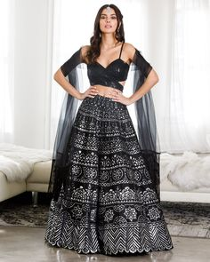 """Give evening wear a whole new meaning this wedding season with this show-stopping lehenga. A full, a-line skirt is decorated with traditional silver patterning and paired with a sequined, wrap-around blouse and organza dupatta. A magical look for any evening occasion. Skirt length is 44"""". To order in another size, see here. Delivery Time: This item is ready to ship and will be dispatched in 1-2 business days after the order is placed. Included In Purchase: Blouse, Skirt, Dupatta Care… Indian Gowns Dresses, Indian Fashion Dresses, Dress Indian Style, Indian Designer Outfits, Designer Dresses, Party Wear Lehenga, Party Wear Dresses, Diwali Outfits, Indian Lehenga"""
