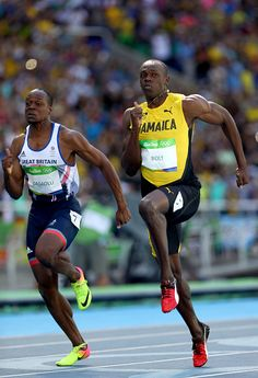 Usain Bolt of Jamaica and James Dasaolu of Great Britain compete in the Men's…