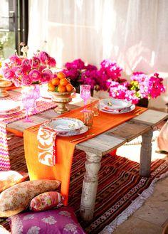 Mesa colorida em tons de laranja e rosa. Ótima ideia para almoço ao ar livre