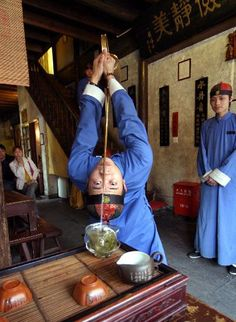 A clerk performs tea art in a tea house in Hangzhou, capital of east China's Zhejiang Province, April 4, 2005. Performances of tea art are presented in a number of tea houses in Hangzhou to attract consumers.