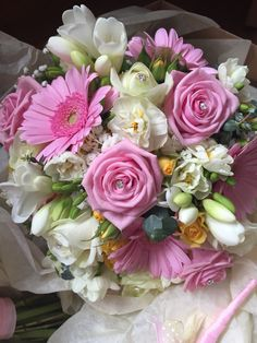 Pink yellow and cream spring bridal bouquet of spray roses, roses, freesia, narcissi, gypsophelia, gerbera and foliage arranged as a handtied