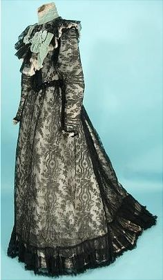 Late Victorian Gown, E. CONWAY Robes, 14 E. 45th Street, New York: ca. 1898, black silk Chantilly lace covering the entire 2-piece gown over a white silk lining.  Trimmed in an aqua velvet on high collar, and around bodice yoke to a velvet bow.  Black sequins cover the net yoke and waistband.
