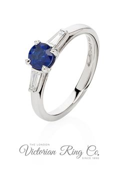 This blue sapphire engagement ring in platinum has tapered baguette cut diamonds either side of the main stone. In this Art Deco design ring, the sapphire is held with four-claws, while the diamonds are in a rubover bezel setting. #BlueSapphire #SapphireRing #SapphireEngagementRing #TaperedBaguettes #ArtDecoRingDesign #ArtDecoEngagementRing #LondonVictorianRingCo