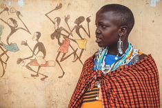Maasai girl in front of a graffiti wall of dancing Maasai people.