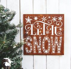 "Time to start thinking of decorating? We are!  ""Let it snow"", this #sign is gorgeous.  We stained the Baltic Birch wood a dark brown, then painted the entire text and #snowflakes in white glittered paint.  A sawtooth hang... #handmade #christmassigns #elfchristmas #elfmovie #reindeernames #christmasdecor #holiday #signage #frozen"