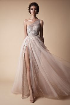 A gorgeous sexy one-shoulder light rose coloured wedding gown with shimmery beaded details, a sexy thigh slit and wispy light tulle // You've seen the sexy yet sweet Muse by Berta 2018 wedding dress collection, now here's Berta's Fall/Winter 2018 evening line of ball gown, fit and flare, and form fitting silhouettes, in case you're looking to slip into something different for your reception.