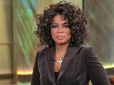 Oprah Winfrey, media mogul, wears a curled hairstyle, with flattering highlights, here.