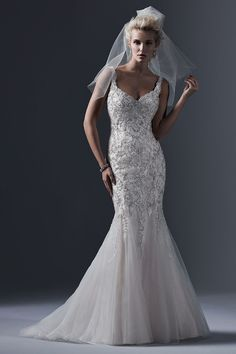 Holland  Lace appliqués, decadently embroidered with dramatic sequins and Swarovski crystals, adorn the bodice of this tulle fit and flare wedding dress, with daring scoop back and romantic sweetheart neckline. Finished with crystal buttons over zipper closure.