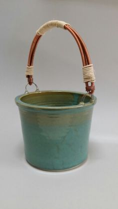 Clay bucket with piano string wire and reed for the handle.