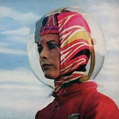 Emilio Pucci's Bubble Helmet was in the days prior to the air-bridge to protect the coiffure from wind and rain on the walk from the terminal to the aircraft. A Braniff International stewardess models the plexiglass headgear at John F, Kennedy Airport, New York in 1965.""