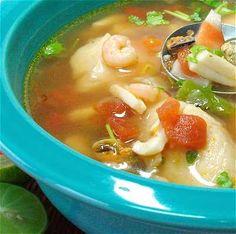 Sopa sencilla de pescado y mariscos /  Easy fish and mixed seafood soup. 1 jitomate mediano 1/2 cebolla pequeña 1 diente de ajo 2 cucharadas soperas de aceite de oliva 2 litros de agua 4 cucharadas soperas de camarón molido (en polvo) 1 taza de verdura mixta picada (zanahoria, papa, chícharos, ejotes, granitos de maíz, etc.) 1 cucharada sopera de sal 600 gramos / 1 1/4 de libra de pescado y/o mariscos varios* un manojo de cilantro limones partidos