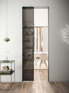 Porta scorrevole interno muro in alluminio grigio ferro e vetro fumè. Stipite raso con effetto filomuro