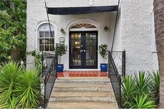 7331 S Claiborne St, New Orleans, LA 70125  inviting front door, french style blue potted trees. nice landscaping