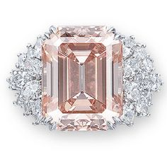 A RARE COLOURED DIAMOND AND DIAMOND RING, BY HARRY WINSTON Set with a rectangular-shaped orangy pink diamond weighing 12.93 carats, to the marquise-cut diamond shoulders, mounted in platinum, ring size 4½ Signed and with maker's mark for Harry Winston