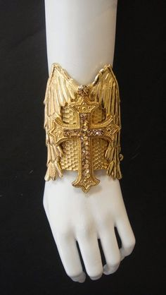 "Wing and Cross Cuff by Marianna Harutunian. ""The original designer of the Gold plated, swarovski crystal wing/cross cuff as seen on Pop Icon Lady Gaga in her ""Judas"" music video. This cuff was also seen in Nicola Formichetti's NY Pop Up Shop."""