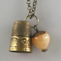 """This is a beautiful antique brass thimble with a wide band of peacock feather detail around the base. It is joined by an acorn crafted of antiqued brass and Honey Jade. The two hang from a 20"""" chain that closes with a lobster clasp and is finished with a 2"""" hearts and flowers extender/back dangle."""