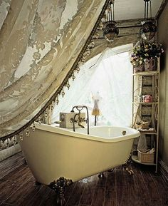 Shabby Chic bathroom at it's best. Beautiful claw foot slipper tub, embellished lacy curtain, and unique lighting make this a  vintage delight.