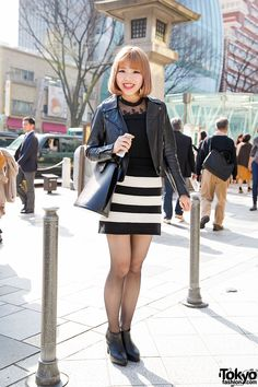 22-year-old Haruka on the street in Harajuku wearing an Azul by Moussy biker jacket over a lace top, a striped mini skirt, a Chanel watch, and ankle boots.