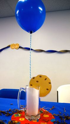 Cookie Monster centerpiece- wrapped balloon sticks; Dollar Tree mug, cookie cutouts, brown crinkle paper and wrapping paper base; white paper and cotton to fill the mug