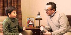 Un niño, que está sentado al lado de la foto de su familia, habla con un hombre que tiene una Biblia en la mano