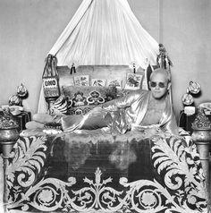 English pop star and pianist Elton John reclines on an elaborately decorated bed, circa Terry O Neill, Paul Newman, Amy Winehouse, Steve Mcqueen, John Lennon, Bowie, Rocketman Movie, Goodbye Yellow Brick Road, Bernie Taupin