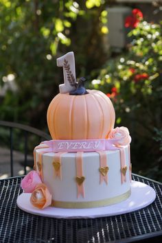 Cute tiered birthday cake with pumpkin top More