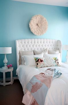 Turquoise blue chic bedroom design with white tufted wingback, white round oval side tables, white lamps, a turquoise blue feature wall, white fuzzy wall art, a pretty throw and silver metallic pillows! I die!