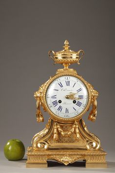 A Napoleon III small gilt bronze mantel clock in Louis XVI style surmounted by a vase and resting on four consoles chiseled with scrolls and laurel garlands. Enamel dial with...