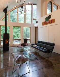 The interior of this modern house is bright and open, with high ceilings and plenty of windows. In the living room, there's a fireplace for cool nights, and sculptural pendant light hanging from the ceiling adds an artistic flair to the space. Pole Barn House Plans, Small House Plans, Interior Walls, Home Interior Design, Hut House, Dome House, Quonset Hut Homes, Arched Cabin, Metal Homes