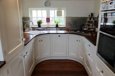 Classic, cottage style kitchen with old fashioned style cupboard doors and wooden bench tops. By Oliver's Kitchens