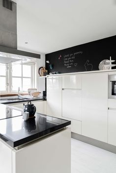 you could never go wrong with white kitchen, black counter top and chalkboard wall