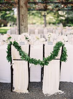 White chair backs with a greenery garland
