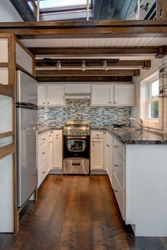 A well equipped tiny house kitchen includes a range, apartment size refrigerator, and upper cabinets.