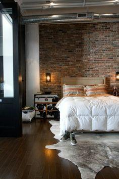 mur de briques chambre a coucher, linge de lit blanc,parquet marron, chambre lumineuse