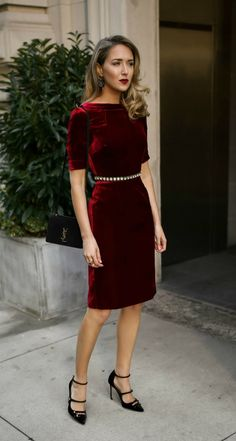 Red velvet sheath dress, embellished black waist belt, black strappy Mary Jane pumps, black leather cross body bag, statement earrings and a dark red lip.