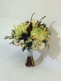 Wedding bouquet made up with white waratahs, leucadendrons, blushing bride, billy buttons, geralton wax and thryptomene.