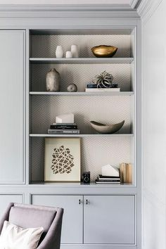 Gray built-in living room cabinets frame styled built-in shelves accented with gray geometric wallpaper.