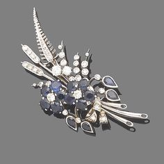 A sapphire and diamond floral spray brooch. The floral spray decorated with circular-cut sapphire and brilliant-cut diamond flowerheads, to a single and similarly-cut diamond surround, diamonds approx. 0.80ct. total, length 5.8cm.